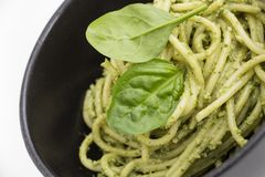 Spaghetti pasta with sauce pesto in black bowl, closeup background. Stock Images