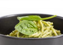 Spaghetti pasta with sauce pesto in black bowl, closeup background. Royalty Free Stock Image