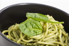 Spaghetti pasta with sauce pesto in black bowl, closeup background. Stock Photography