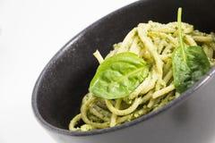 Spaghetti pasta with sauce pesto in black bowl, closeup background on white. Spaghetti pasta with sauce pesto in black bowl, closeup background on white Royalty Free Stock Photos