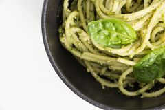Spaghetti pasta with sauce pesto in black bowl, closeup background on white. Stock Images