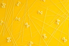 Italian pasta background. Spaghetti pasta is scattered on a yellow background. Top view, flat lay Royalty Free Stock Images