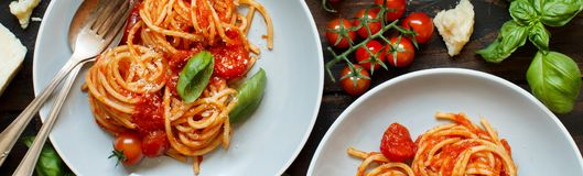 Spaghetti pasta with tomato sauce, basil and cheese on a wooden table royalty free stock image