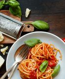 Spaghetti pasta with tomato sauce. Basil and cheese on a wooden table top view royalty free stock images