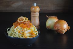 Spaghetti pasta with tomato sauce and basil. On plate on dark table stock images