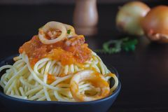 Spaghetti pasta with tomato sauce and basil. On plate on dark table royalty free stock images