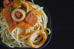 Spaghetti pasta with tomato sauce and basil. On plate on dark table stock photography