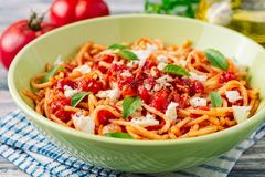 Spaghetti pasta with tomato sauce, mozzarella cheese and fresh basil leaves on white-blue vintage wooden background royalty free stock photo