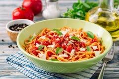 Spaghetti pasta with tomato sauce, mozzarella cheese and fresh basil leaves on white-blue vintage wooden background stock image