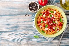 Spaghetti pasta with tomato sauce, mozzarella cheese and fresh basil leaves on white-blue vintage wooden background royalty free stock images
