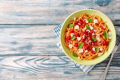 Spaghetti pasta with tomato sauce, mozzarella cheese and fresh basil leaves on white-blue vintage wooden background stock photography