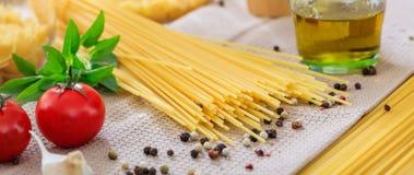 Spaghetti pasta, tomatoes, garlic and pepper seeds, banner. Italian food preparation. Spaghetti pasta, tomatoes, garlic and pepper seeds, banner royalty free stock photo