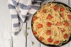 Spaghetti pasta with tomatoes and parsley on wooden table Royalty Free Stock Images