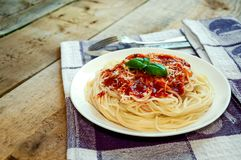 Spaghetti Pasta With Tomato Sauce, Cheese And Basil On Wooden Table. Traditional Italian Food Stock Photo