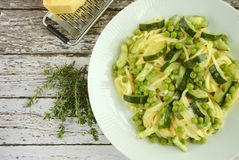 Spaghetti pea zucchini. Spaghetti garlic thyme with peas, zucchini and parmesan cheese Royalty Free Stock Photography