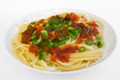 Spaghetti with pepper sauce on plate. Spaghetti with grenn pepper and tomato sauce on plate stock images