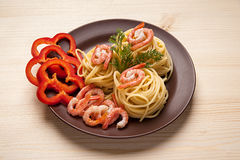 Spaghetti with pepper and shrimp. Spaghetti with red pepper and shrimp in a dish on the table Royalty Free Stock Photos