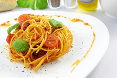 Spaghetti pesto rosso. Fresh spaghetti with pesto rosso and sliced tomatoes Stock Images