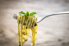 Spaghetti with pesto sauce and basil leaf on the fork Stock Images