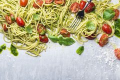 Spaghetti with pesto sauce, roasted cherry-tomatoes, fresh basil and parmesan cheese on steel background Stock Photos