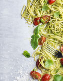 Spaghetti with pesto sauce, roasted cherry-tomatoes, fresh basil and parmesan cheese on steel background Stock Photography
