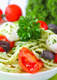Spaghetti with pesto sauce and tomato Stock Photos
