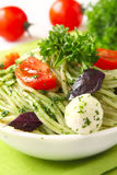 Spaghetti with pesto sauce, tomato and cheese Stock Photos