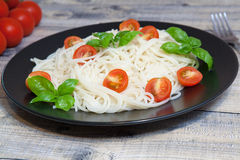 Spaghetti. On a plate with cherry and basil Stock Image