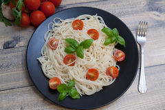 Spaghetti. On a plate with cherry and basil Royalty Free Stock Images