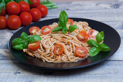 Spaghetti. On a plate with cherry and basil Stock Photos