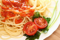 Spaghetti. On a plate with tomato sauce and tomatoes with green parsley . Close-up Royalty Free Stock Images
