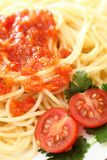 Spaghetti. On a plate with tomato sauce and tomatoes with green parsley. Close-up Royalty Free Stock Image