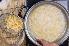 Spaghetti podnoszący dalej zimna woda z colander obrazy stock