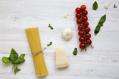 Spaghetti, pomodori, basilico, parmigiano, aglio Ingredienti per la cottura della pasta su una tavola di legno bianca, disposizio Fotografia Stock