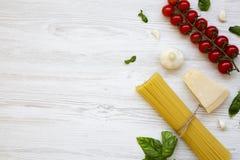 Spaghetti, pomodori, basilico, parmigiano, aglio Ingredienti per la cottura della pasta su una tavola di legno bianca, disposizio Fotografia Stock Libera da Diritti