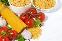 spaghetti, pomodori ed ingredienti freschi su una tavola bianca immagine stock libera da diritti