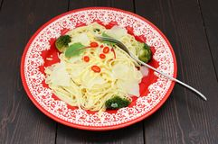 Spaghetti with potatoes, broccoli, chili and chard in red plate Stock Photo