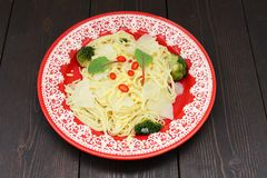 Spaghetti with potatoes, broccoli, chili and chard in red plate Royalty Free Stock Photo