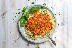 Spaghetti with prawns in tomato sauce Stock Photos
