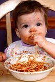 Spaghetti Queen #2. Adorable baby sitting in high chair eating a bowl of spaghetti royalty free stock photos