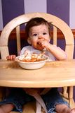 Spaghetti Queen #3. Adorable baby sitting in high chair eating a bowl of spaghetti stock image