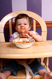 Spaghetti Queen #4. Adorable baby sitting in high chair eating a bowl of spaghetti Stock Photos