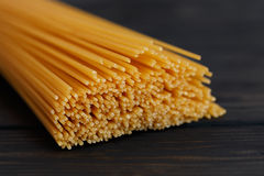 Spaghetti raw food in dark background on side view. Close-up spaghetti raw food in dark background on side view Stock Photos