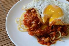 Spaghetti with red chicken tomato sauce topping with fried egg. On white plate Royalty Free Stock Photo
