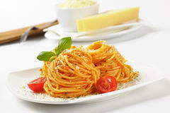 Spaghetti with red pesto and parmesan cheese Stock Photos
