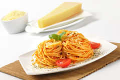 Spaghetti with red pesto and parmesan cheese Stock Photo