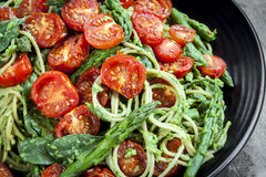 Spaghetti with Roasted Tomatoes and Asparagus Pesto. Spaghetti with roasted tomatoes, spinach, and asparagus pesto.  Overhead view food background Royalty Free Stock Image