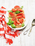 Spaghetti with roasted tomatoes and fresh basil over white background Royalty Free Stock Image