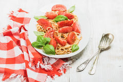 Spaghetti with roasted tomatoes and fresh basil over white background Stock Photography