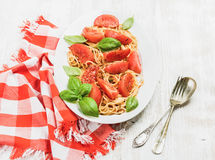 Spaghetti with roasted tomatoes and fresh basil over white background Royalty Free Stock Photos
